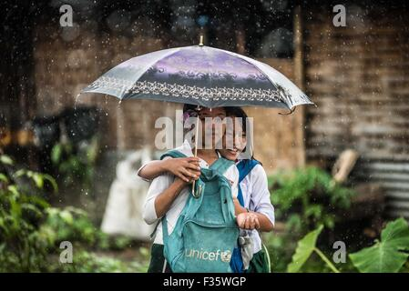 Girls smile as they walk back from school during a rain storm in Myanmar - Stock Image