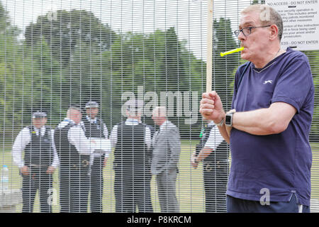 Regent's Park London, 12th July 2018. Police assemble in a fenced off area behind protesters. Demonstrators are protesting against US President Donald Trump's visit to London at Hanover Gate, close to Winfield House, the US ambassador's residence where Trump is expected to spend some time today. Credit: Imageplotter News and Sports/Alamy Live News - Stock Image
