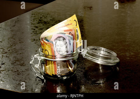 Australian Dollars in a glass jar on a kitchen counter - Stock Image