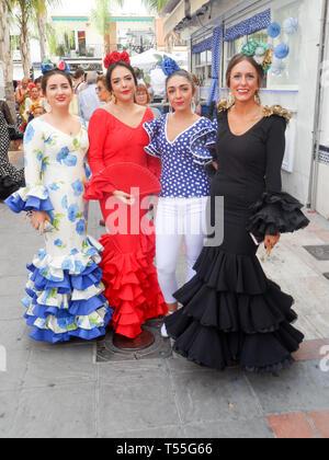 Local Spanish women dressed in traditional flamenco dresses attending the Feria del Rosario. An annual comunity fair in Fuengirola, Costa del sol, - Stock Image