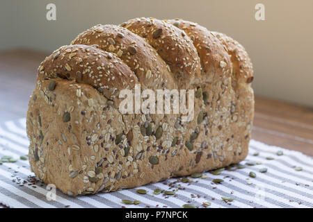 Single loaf of seeded multigrain bread sitting on striped cloth - Stock Image