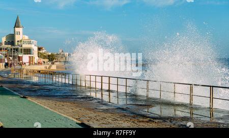Spray from waves splashing on boardwalk leading to Tamariz beach in the Atlantic resort town of Estoril near Lisbon, Portugal. - Stock Image