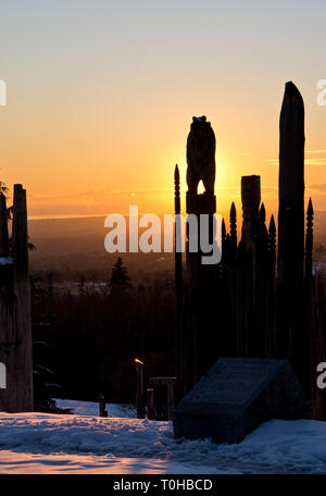 Burnaby Mountain Park in Winter.  Burnaby, British Columbia, Canada. Japanese Ainu totems called 'Playground of the Gods', backlit by the sunset. - Stock Image