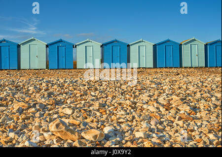 Charmouth, Dorset and a line of beach huts in alternating light and dark blue colours at the back of the shingle - Stock Image