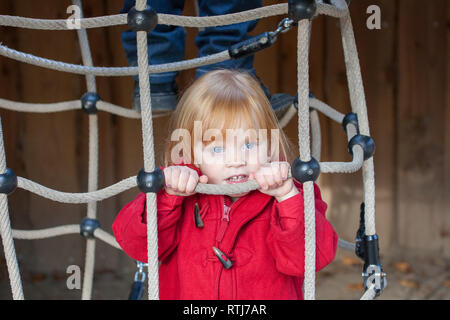 Girl playing on a rope web - Stock Image