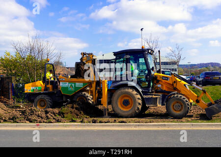 Workmen using a JCB 3CX excavator loading excavated topsoil into a dumper truck for removal - Stock Image