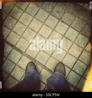 Black sneakers and blue jeans on pavement with square geometric patterned tiles. Grunge texture overlay with vintage - Stock Image