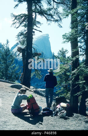 Hikers take a break on the trail to look at distant Half Dome, Yosemite National Park, California - Stock Image