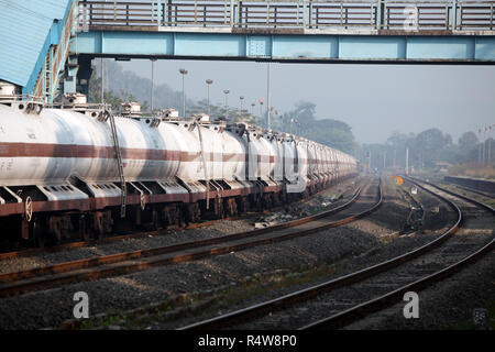 A train carrying fuel stationed around a curve at a railway station in India, in morning. - Stock Image