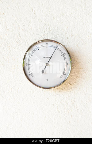 Outdoor thermometer showing 20 degrees Celsius temperature on white wall. - Stock Image