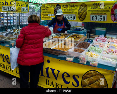 Woman buying Greek or Turkish Food from a market stall in Northallerton North Yorkshire - Stock Image