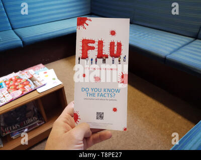 A leaflet with advice for patients about Flu is seen in an NHS local doctors surgery waiting room in Warwickshire, UK, On May 14, 2019. - Stock Image