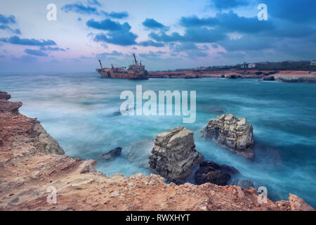 Rocks in sea with abandoned ship on background near Paphos, Cyprus  (with HDR-effect) - Stock Image