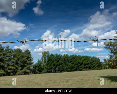 A close up of a section of barbed wire fence with trees sky and field in the background - Stock Image