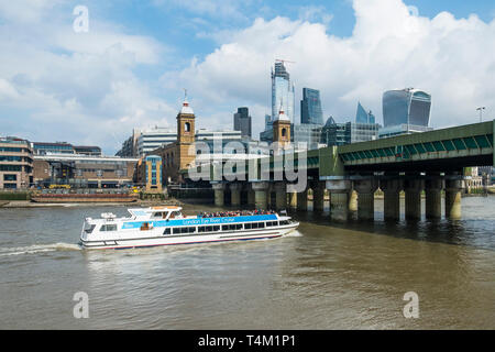 A tourist boat from the London Eye River Cruise passing under Cannon Street Bridge on the River Thames in London. - Stock Image
