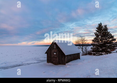 Snow-covered wooden cabin on the shore of icy Lake Superior. Duluth, Minnesota, USA. - Stock Image