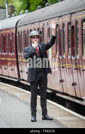 A train guard at Haworth train station during the Haworth 40s weekend. - Stock Image