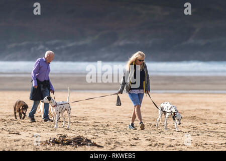Dog walkers on Crantock Beach in Newquay in Cornwall. - Stock Image