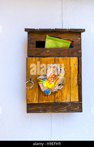 A mailbox in France with colourful mail sticking out. Seen in the village of Ramatuelle, South of France - Stock Image