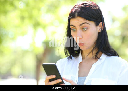Perplexed woman reading smart phone content in a park with a green background - Stock Image