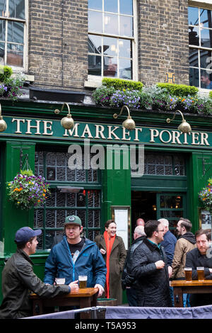 Customers drinking outside the Market Porter public house in Borough Market in London. - Stock Image