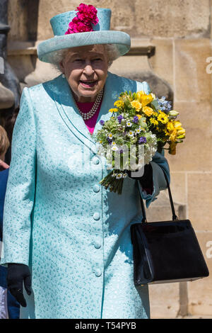 Windsor, UK. 21st April 2019. The Queen prepares to leave after being presented with a traditional posy of flowers by two young boys outside St George's Chapel in Windsor Castle following the Easter Sunday service. Credit: Mark Kerrison/Alamy Live News - Stock Image