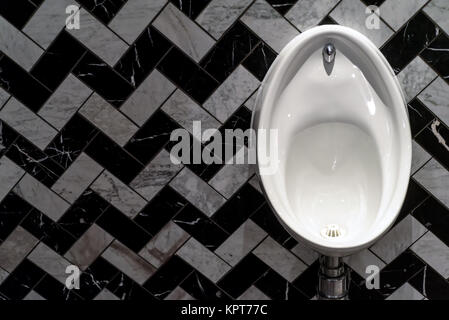 Single white male urinal in white porcelain with a tiled pattern in black and white in herringbone style - Stock Image