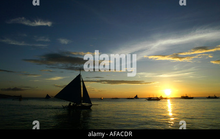 Sailboats off of White beach at sunset in Boracay, Philippines. - Stock Image