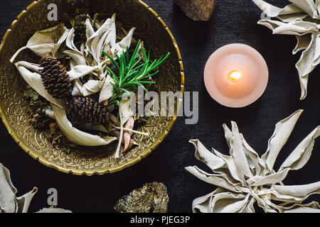 Bowl of Mixed Herbs with White Sage and Pyrite on Black Wood - Stock Image