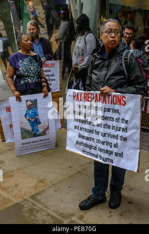 London, UK. 13th August 2018. Protesters outside the offices of Legal & General. Three days before the 6th anniversary of the massacre when 34 striking miners were shot dead by South African police at Lonmin's Marikana platinum mine, a tour of the City of London visited investors, insurers and shareholders profiting from the violence against people and nature in Marikana and heard about the colonial roots of the huge wealth of the City. Credit: Peter Marshall/Alamy Live News - Stock Image