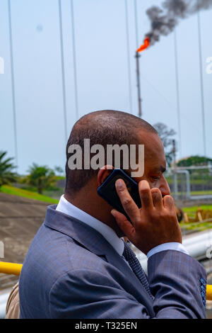 A businessman in a suit talks on his phone in front of the Punta Europa oil and gas complex in Equatorial Guinea - Stock Image