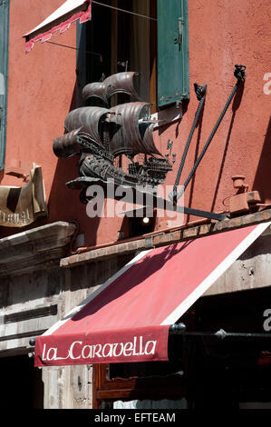 Bronze model of a sailing ship over the awning of La Caravella Restaurant on Calle XXII Marzo Venice Italy - Stock Image