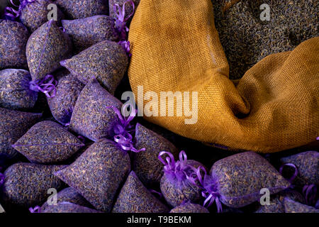 Small violet bags with aromatic seeds of lavender plant on market in Provence, close up - Stock Image