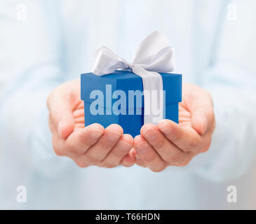 Small blue present box in hands - Stock Image