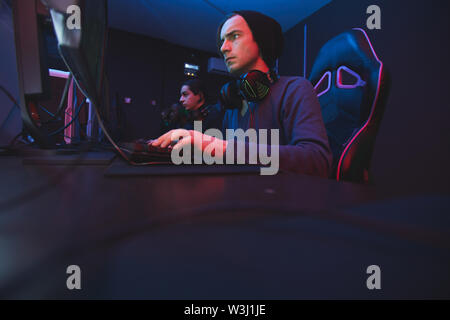 Serious concentrated young hipster man in black beanie sitting at table and pushing buttons of keyboard while participating in esports tournament - Stock Image
