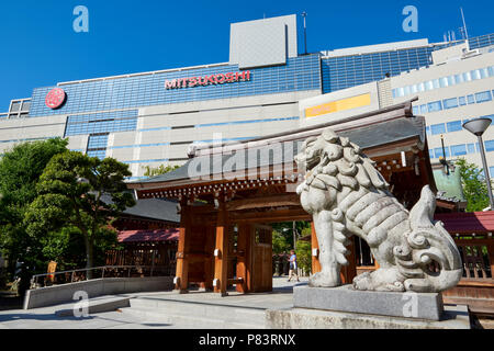 Low angle shot of komaine dog statues in Kego Shrine with modern shop buildings in the background. In Tenjin, central Fukuoka, Japan - Stock Image