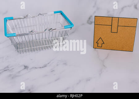 shopping basket with mini cardboard delivery parcel box on marble desk with fairy lights, concept of online purchases and shipping - Stock Image