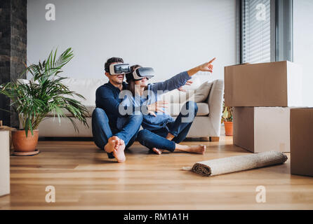 A young couple with VR goggles sitting on a floor, moving in a new home. - Stock Image