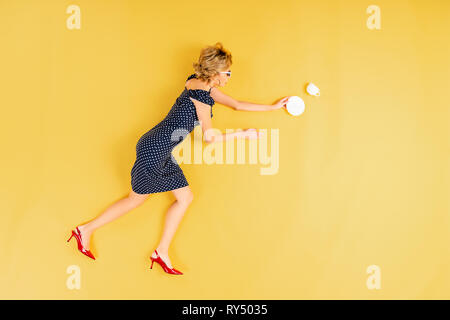 Blonde woman in dress with saucer and cup lying on yellow background - Stock Image