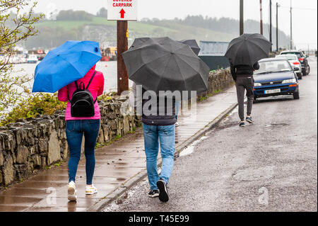 Bantry, West Cork, Ireland. 14th Apr, 2019. People walk in the rain in Bantry this afternoon.  County Cork is currently in the midst of a Status Yellow Rainfall and Wind Warning which lasts until 6pm Monday. Credit: Andy Gibson/Alamy Live News. - Stock Image