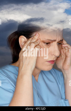Middle aged woman suffering from an acute headache or migraine attack due to weather sensitivity - Stock Image