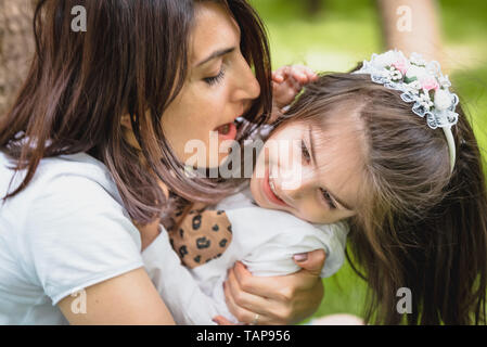Young mom hugs and has fun with her daughter while embracing.Happy mother hugging her daughter with love and natural emotion. - Stock Image
