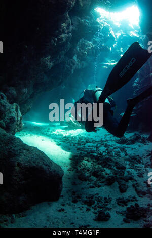 Underwater photograph of a scuba diver with Cressi fins swimming through a cave in the red sea, Egypt. - Stock Image