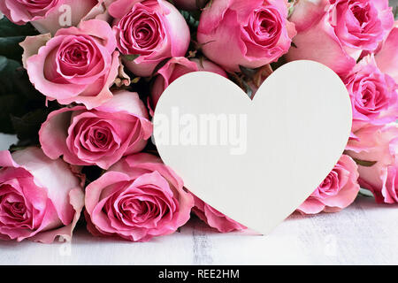 Beautiful retro soft pink rose flower background with wooden heart and room for text. - Stock Image