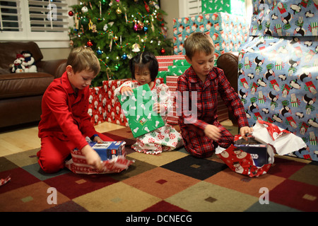 Three children opening gifts on Christmas day - Stock Image