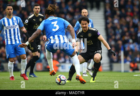 Japanese forward Shinji Okazaki of Leicester challenges Gaetan Bong of Brighton during the Premier League match between Brighton and Hove Albion and Leicester City at the American Express Community Stadium in Brighton and Hove. 31 Mar 2018 *** Editorial use only. No merchandising. For Football images FA and Premier League restrictions apply inc. no internet/mobile usage without FAPL license - for details contact Football Dataco *** - Stock Image