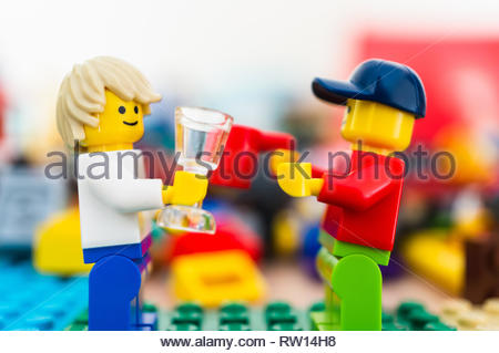 Poznan, Poland - February 15, 2019: Two Lego man character figures holding glass and cup and looking at each other while having a talk. - Stock Image