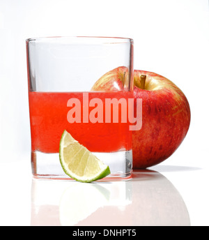 A colorful cocktail drink in a glass with a wedge of lime and a whole red apple. - Stock Image