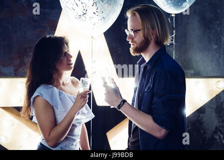 Young coupl celebrates their love toasting with champagne glass with a hollywood style backlight, postprocessing - Stock Image