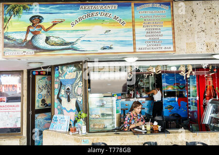 Cartagena Colombia El Laguito restaurant neighborhood family business Sabores del Mar typical food Hispanic resident residents woman eating black merm - Stock Image